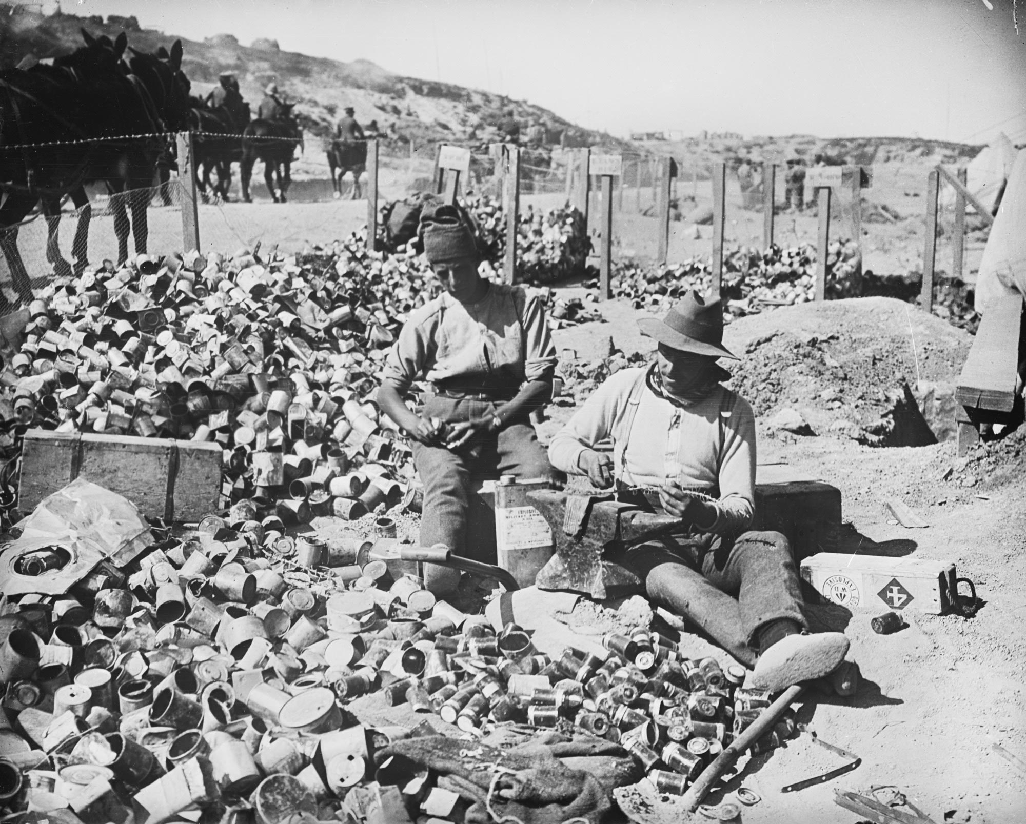 <p>Two soldiers cutting up barbed wire for jam tin bombs, Gallipoli, 1915</p>