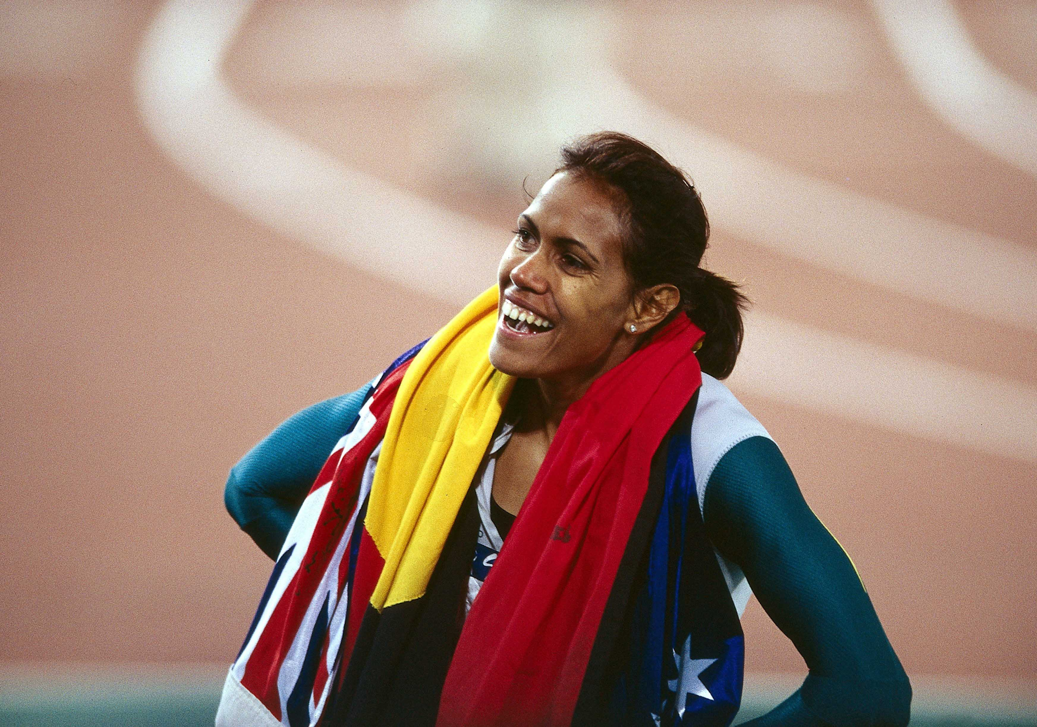 Cathy Freeman after winning the 400m final at the Sydney Olympics, with the Australian and Aboriginal flags around her shoulders, 25 September 2000